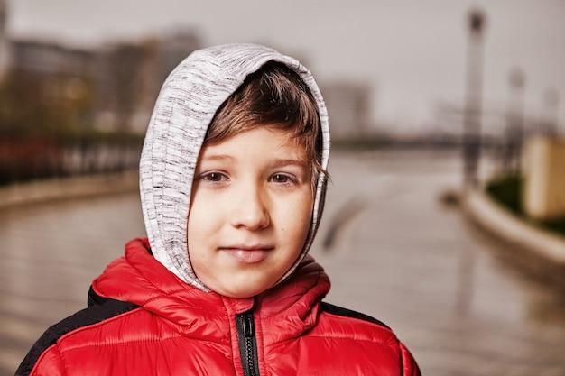 屋外で暖かい服を着た7歳の子供の肖像画。