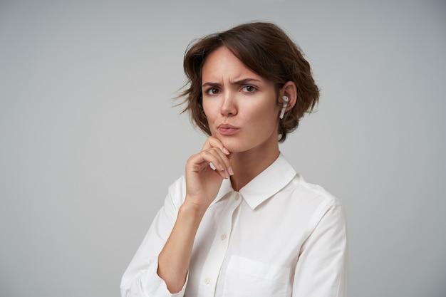 Портрет суровой молодой брюнетки с повседневной прической, держащей подбородок поднятой рукой и сомнительно выглядящей, стоящей в строгой одежде