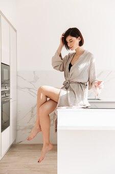 부엌에서 포즈 짧은 검은 머리를 입고 성적 우아한 여자의 초상화, 맑은 아침에 테이블에 앉아