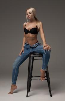 彼女の魅力的な腹を見せてくれるブルーブランドのジーンズを着て素晴らしい姿のセクシーな美しいブロンドの肖像画。灰色の背景に分離
