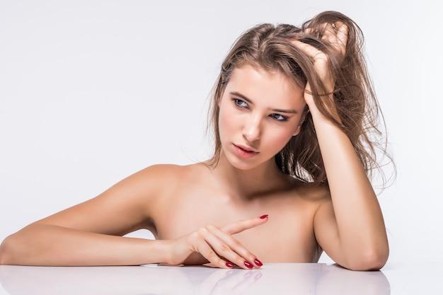 白い背景で隔離のファッション髪型と服をせずにセクシーなブルネットモデルの女の子の肖像画