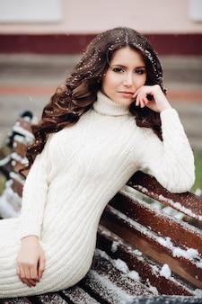 白いドレスでポーズをとってセクシーなブルネットの肖像画。ベンチに座っている巻き毛の美しい若い女性。カメラを見て、セクシーな表情、メイクを打つ。