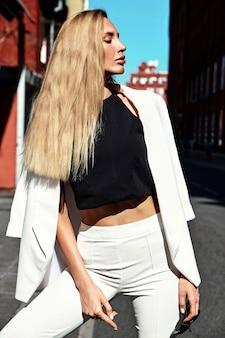 Портрет сексуальной модной современной бизнес-леди в белом костюме позирует на фоне улицы за голубым небом