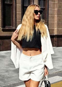 Портрет сексуальной модной современной бизнес-леди модели в белом костюме позирует на фоне улицы