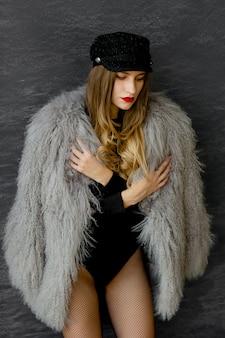 ラマ、ボディスーツ、レースタイツの黒い帽子と灰色のコートを着たセクシーな女の子の肖像画。