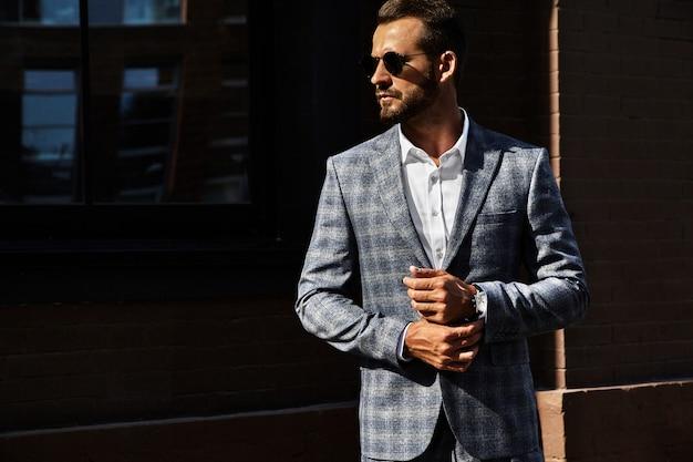 通りの背景にポーズをとってエレガントな市松模様のスーツに身を包んだセクシーなハンサムなファッションビジネスマンモデルの肖像画。メトロセクシャル