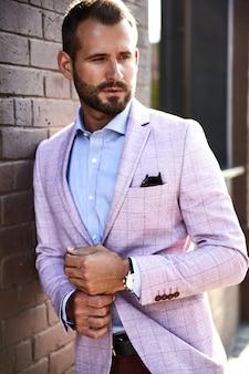 Портрет сексуальный красивый модный бизнесмен модель, одетый в элегантный костюм, позирует возле кирпичной стены на фоне улицы. метросексуал