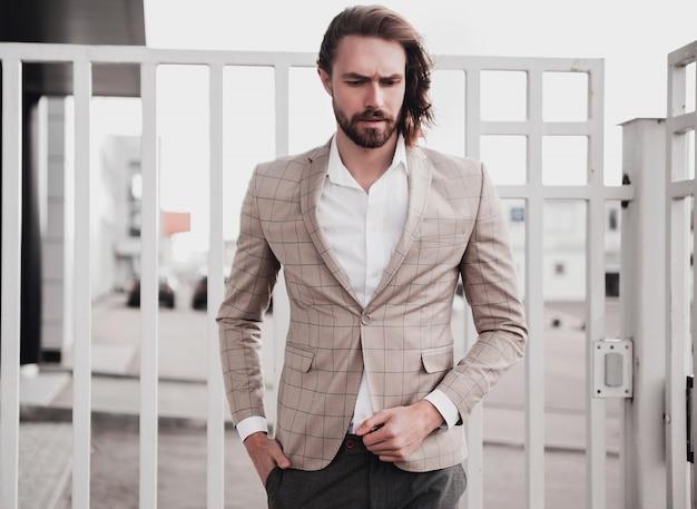 通りの背景にポーズをとってエレガントなベージュの市松模様のスーツに身を包んだセクシーなハンサムなファッション男性モデル男の肖像