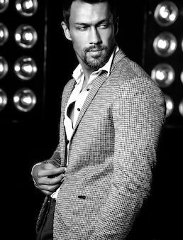 검은 스튜디오 조명 배경에 우아한 양복을 입고 섹시한 잘 생긴 패션 남성 모델 남자의 초상화