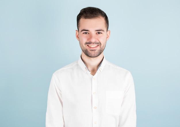 青い背景の上に立っている白いカジュアルシャツのセクシーな男の肖像画
