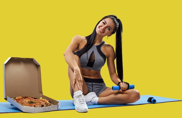 片手にダンベルを持って笑顔のフィットネスマットの新鮮なおいしいピザの箱の近くに座っているスポーツウェアのセクシーな筋肉ビルドフィット女性の肖像画