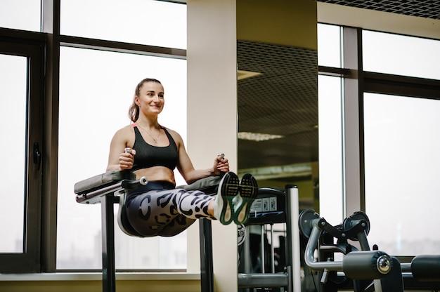 Портрет сексуальной мускулистой девушки в спортивной одежде, делающей упражнения на штанге, поднимает ноги вверх, упражнения на пресс в тренажерном зале