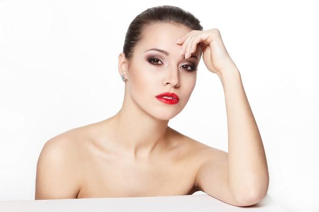 グラマーの赤い唇、明るいメイク、アイ矢印メイク、純度の顔色でセクシーな座っている白人の若い女性モデルの肖像画。完璧なきれいな肌
