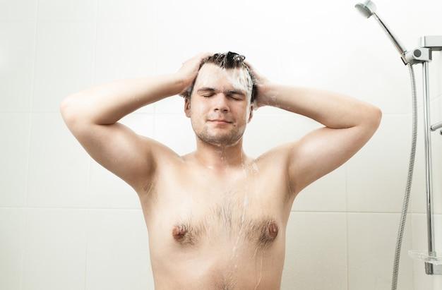 Портрет сексуального улыбающегося человека, мытье волос в душе