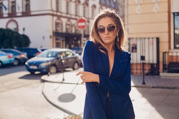 화창한 가을 날에 선글라스를 착용하는 파란색 정장을 입고 거리를 걷는 섹시한 세련된 여자의 초상화