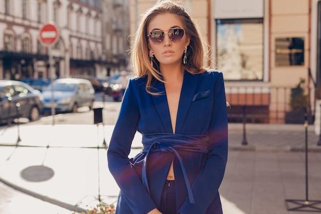 晴れた秋の日にサングラスをかけて青いスーツを着て通りを歩くセクシーなスタイリッシュな女性の肖像画