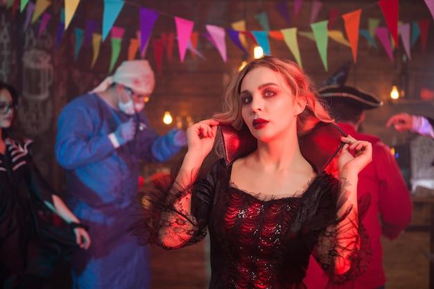 ハロウィーンのイベントで魔女の衣装を着たセクシーな女性の肖像画。バックグラウンドで怖い医者。