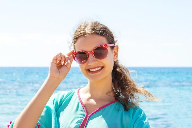 바다에서 엄지 손가락을 보여주는 선글라스에 섹시 한 여자의 초상화.