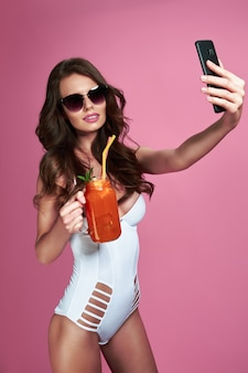 飲み物を保持し、ピンクの壁にselfieショットをしているサングラスを身に着けている白い水着モノキニのセクシーな女性の肖像画