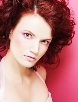 Портрет сексуальной женщины с красивым макияжем и рыжими вьющимися волосами.