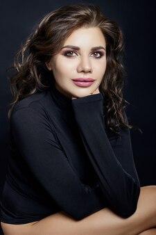 Портрет сексуальной женщины с черным свитером с высоким воротом и длинным воротником на сером фоне крупным планом. красивая девушка с вьющимися волосами, большие красивые глаза и шикарная улыбка