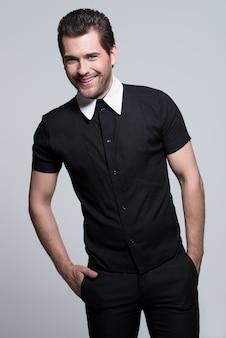 주머니에 손 가진 검은 셔츠에 섹시 한 젊은 행복 한 남자의 초상화 회색 벽에 포즈.