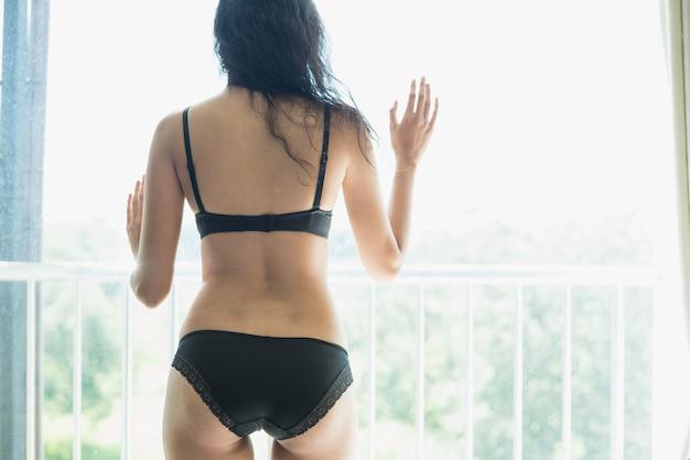 침실에서 비키니를 입고 섹시한 젊은 여성 모델의 초상