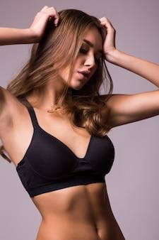 Портрет сексуальной молодой женщины с ее руками на бедрах. женщина фитнеса с мускулистым телом готова на серой стене