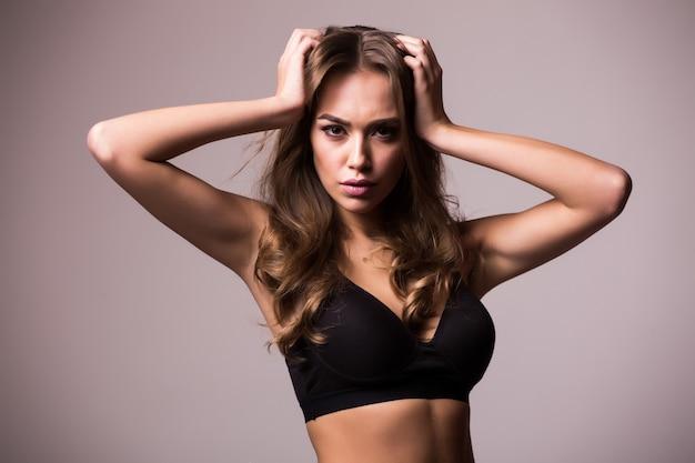 엉덩이에 그녀의 손으로 섹시 한 젊은 여자의 초상화. 근육질 몸매가 회색 벽에 준비된 피트니스 여성