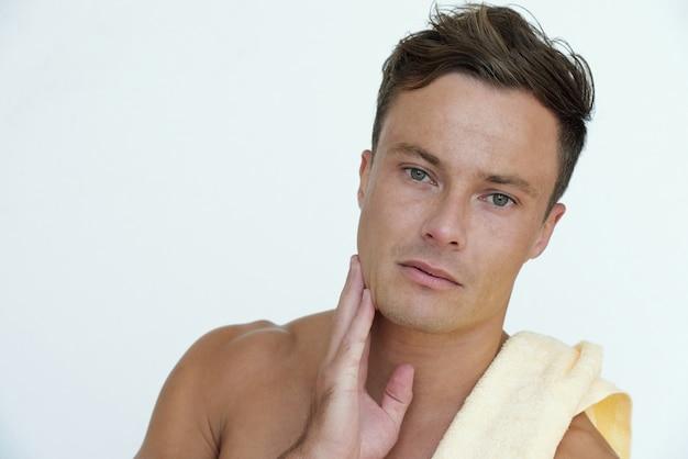 朝のシャワーの後に彼の顔の柔らかい肌に触れる上半身裸の魅力的な真面目な若い男の肖像画