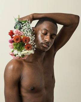 花の花束でポーズをとって上半身裸の男の肖像画
