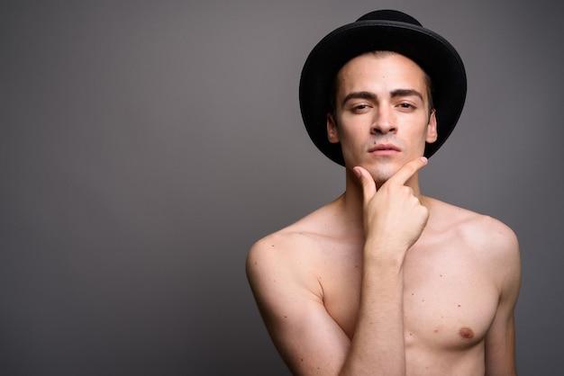 灰色のスタジオの背景に対して帽子をかぶっている上半身裸の男の肖像