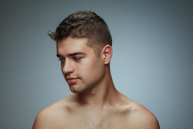 灰色の背景に分離された上半身裸の若い男の肖像画。側面を見てポーズをとる白人の健康な男性モデル。