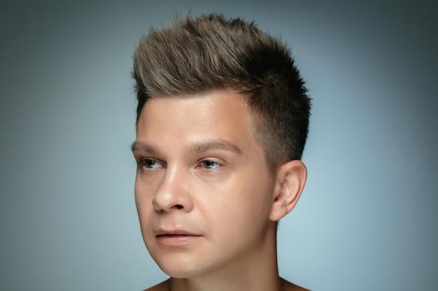 灰色の背景に分離された上半身裸の若い男の肖像画。