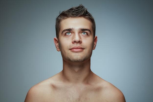 灰色のスタジオの背景に分離された上半身裸の若い男の肖像画。見上げてポーズをとる白人の健康な男性モデル。男性の健康と美容、セルフケア、ボディケア、スキンケアのコンセプト。