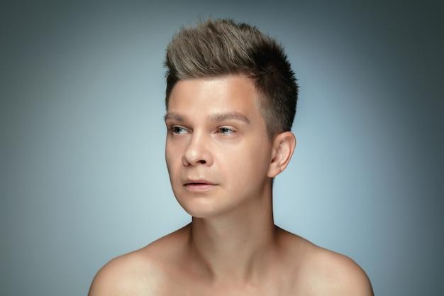 灰色のスタジオの壁に分離された上半身裸の若い男の肖像画