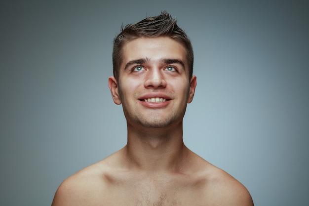 灰色のスタジオで隔離の上半身裸の若い男の肖像画