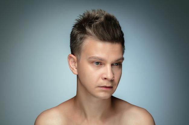 회색 벽에 고립 된 벗은 젊은 남자의 초상화. 백인 건강한 남성 모델 측면을보고 포즈. 남성의 건강과 미용, 셀프 케어, 바디 및 스킨 케어의 개념.