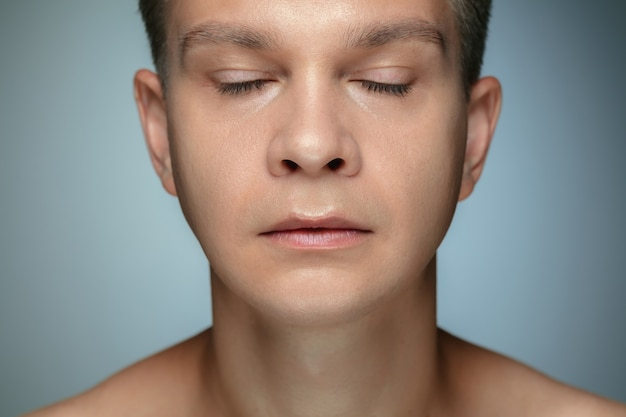 회색 벽에 고립 된 벗은 젊은 남자의 초상화. 눈을 가진 포즈 백인 건강한 남성 모델 폐쇄. 남성의 건강과 미용, 셀프 케어, 바디 및 스킨 케어의 개념.