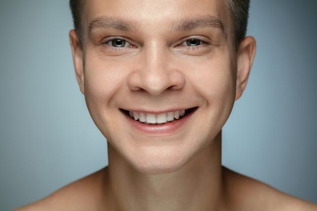 灰色の壁に分離された上半身裸の若い男の肖像画