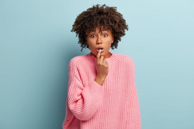 ショックを受けたアフリカ系アメリカ人の女性の肖像画は、不思議から息を呑み、唇に指を置き、言葉を失い、心配そうな表情で何かを聞き、ピンクのジャンパーを着て、屋内でモデルを作ります。 omgのコンセプト