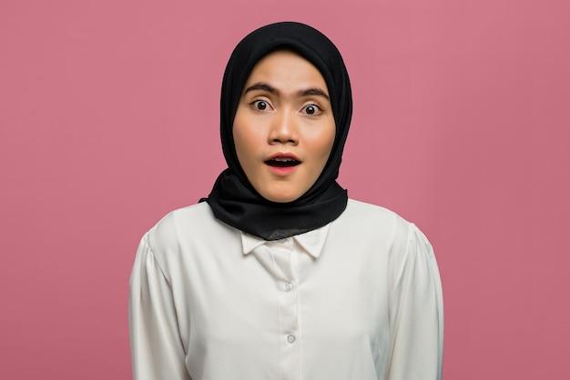 Портрет потрясенной красивой азиатской женщины в белой рубашке