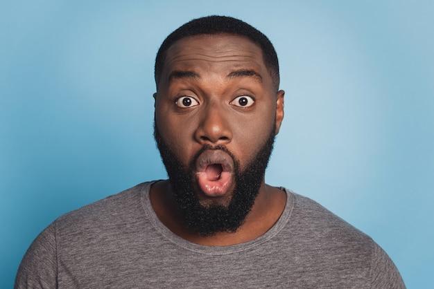 충격을 받은 흑인 남성 열린 입의 초상화는 믿을 수 없는 나쁜 소식을 듣습니다.