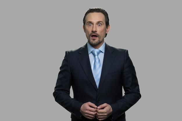 灰色の背景にショックを受けたビジネスマンの肖像画。口を開けて驚いたハンサムなビジネスマン。