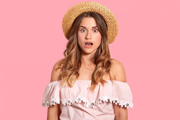 Портрет потрясен кавказской женщины носит соломенную шляпу и модную блузку, показывает голые плечи, изолированные на розовой стене, удивлен испортить отпуск. omg и концепция реакции.