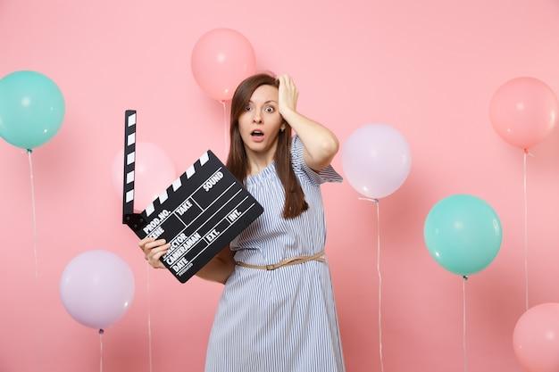 カラフルなエアバルーンでピンクの背景にカチンコを作る古典的な黒いフィルムを保持している頭にしがみついている青いドレスで口を開けてショックを受けた心配している女性の肖像画。誕生日ホリデーパーティー。