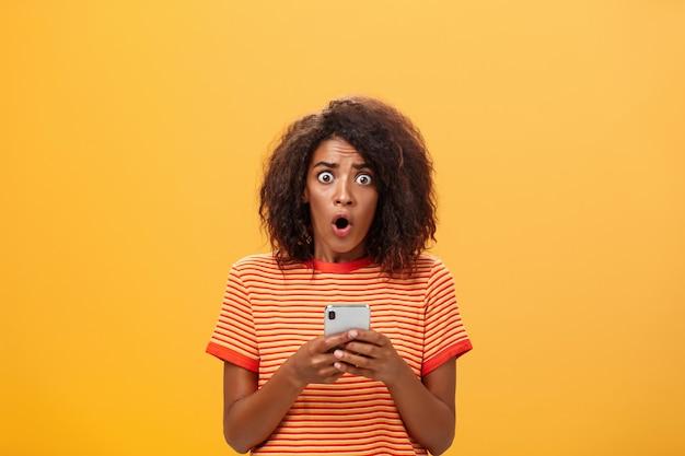 スマートフォンを持ってアフロヘアスタイルでショックを受けた浅黒い肌の女性の肖像画。