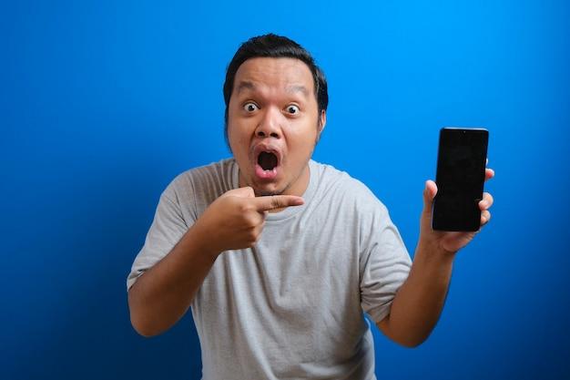 Портрет потрясенного толстого азиатского мужчины в серой футболке, указывающего на мобильный телефон и смотрящего в камеру с изумлением, удивленного тарифами на мобильные данные. студийный снимок, изолированные на синем фоне