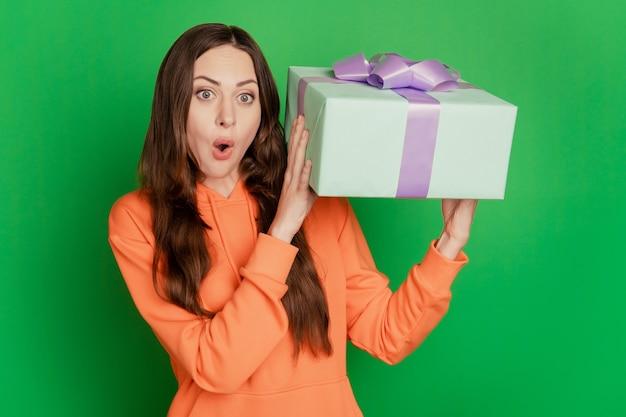 Портрет потрясенной смешной дамы держит подарочную коробку открытым ртом на зеленом фоне
