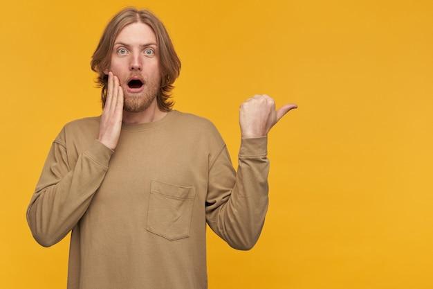 金髪の髪型とあごひげを持つショックを受けた男の肖像画。ベージュのセーターを着ています。彼の顔に触れます。黄色の壁の上に隔離されたコピースペースで右に親指を向ける